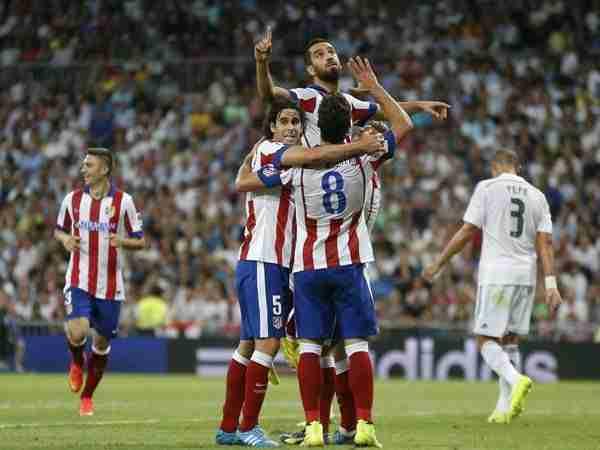 Los compañeros alzan a Arda Turan tras marcar al Real Madrid