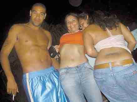 Adriano Leite posando con dos mujeres