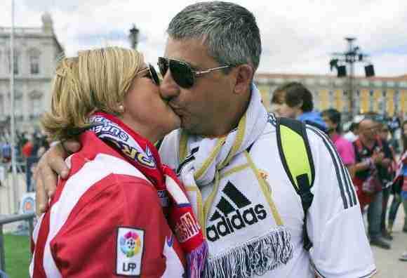 Aficionados de Real Madrid - Atlético besándose
