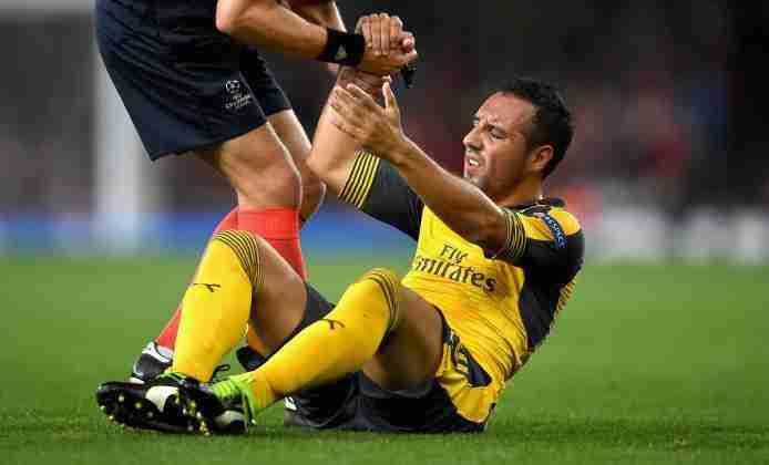 Santi Cazorla ayudado a ser levantado durante un partido de la Premier League