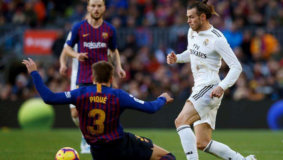 Gareth Bale y Gerard Piqué disputan balón